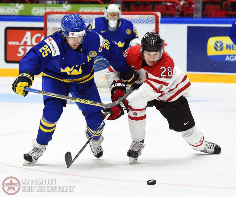 Sweden's Axel Holmstrom #25 battles for a loose puck with Canada's Lawson Crouse #28 during preliminary round action at the 2016 IIHF World Junior Championship. (Photo by Matt Zambonin/HHOF-IIHF Images)
