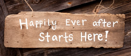cute handmade wooden wedding sign against old building saying happily ever after starts here - CROPPED