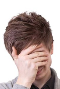 A young man in a gray cardigan shows facepalm