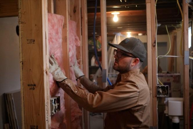 Jesse Installing batt insulation on interior bathroom wall