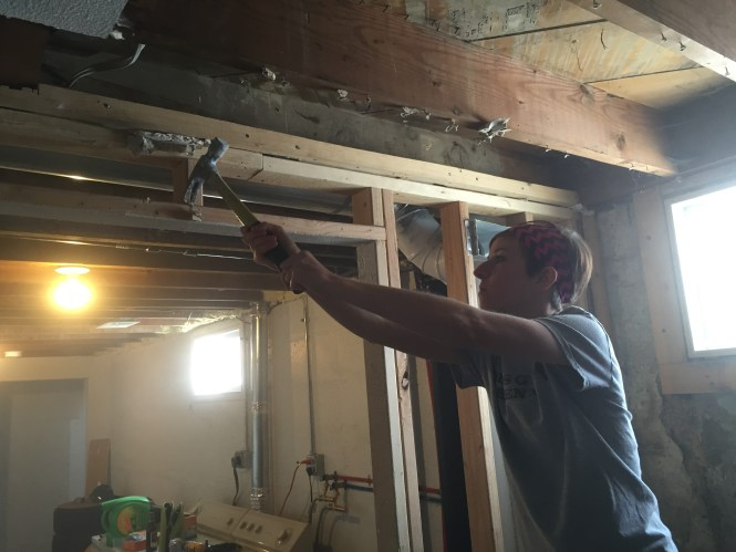 Kelly removing nails and screws from exposed framing