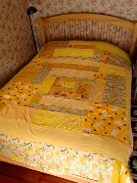 yellow quilt on bed  105