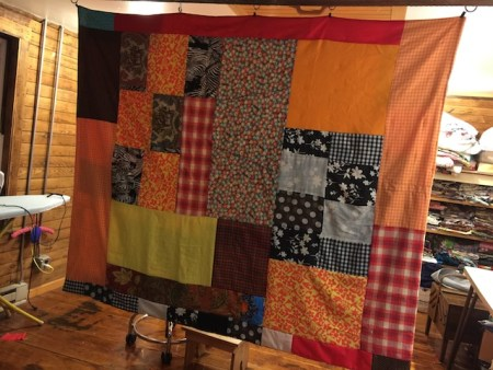 I hang the quilt from my ceiling when I'm tacking it. I'm using orange yarn.