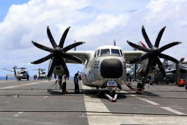 El C-2A de transporte que desarrolló el grueso de los traslados de personal y visitantes visto a su paso por Panamá. En segundo plano, dos MH-60S de escuadrón HSC-4 aprontándose para despegar (foto: Embajada de EE.UU. en Panamá).