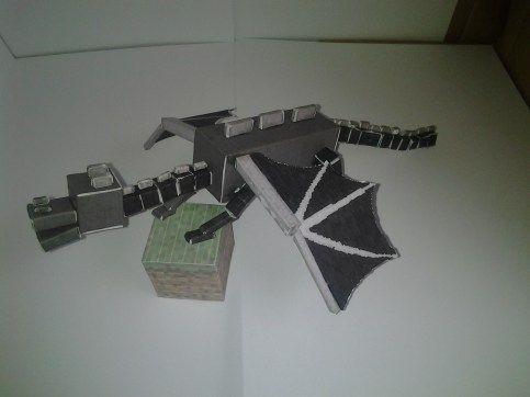 Side view of Enderdragon papercraft on a grass block cutout
