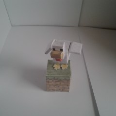 chicken papercraft model on a grass cutout block