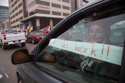 Kelly Dean a teacher from Lansing joins protestors as they block traffic around the Michigan State Capitol building in Lansing on April 15, 2020.
