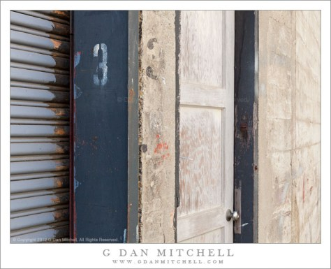 Door Number Three - A loading dock door (#3) and a dilapidated and worn side door in a concrete wall, San Francisco.