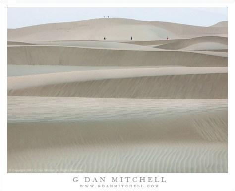 Walkers contemplate evening light on sand dunes