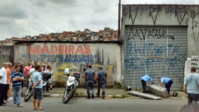 Amigos e parentes observam funcionários do IML (Instituto Médico Legal) retirando corpo do ex-jogador Alves