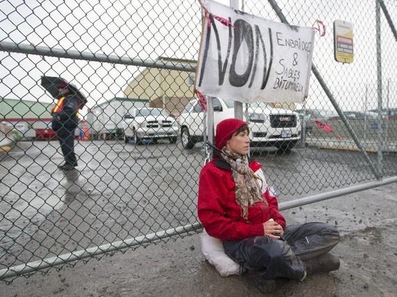 Former Greenpeace intern Alyssa Symons Belanger locked to a gate