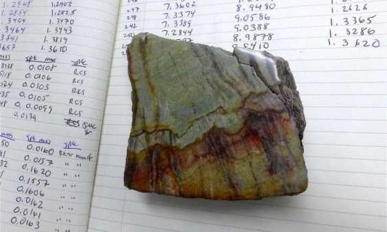 This sample of 3.26-billion-year-old barite shows the granular barite (gray-green areas) that was influenced by ocean water, and bladed barite (vertical black bands) that was by ocean water and water circulating below the sea floor. Credit: David Tenenbaum