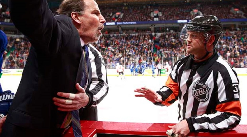 VANCOUVER, BC - JANUARY 18: Referee Kyle Rehman #37 talks to head coach John Tortorella of the Vancouver Canucks who is shouting at the Calgary Flames' bench during their NHL game at Rogers Arena January 18, 2014 in Vancouver, British Columbia, Canada.  Vancouver won 3-2. (Photo by Jeff Vinnick/NHLI via Getty Images)
