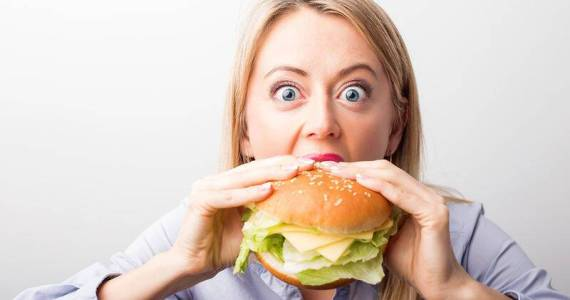 bigstock-Woman-eating-burger-120861863