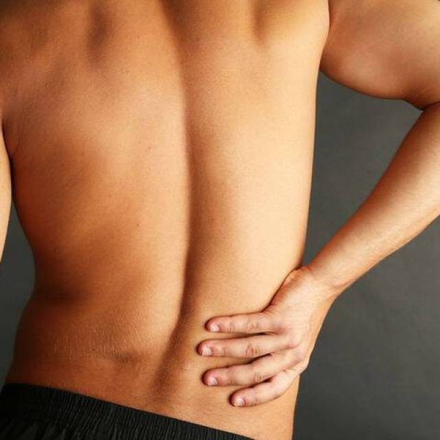 bigstock-Young-man-with-back-pain-on-gr-52560715