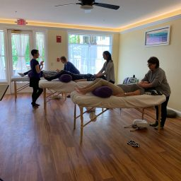 Classroom with adult students practicing Reiki on three bodywork tables while instructor looks on.