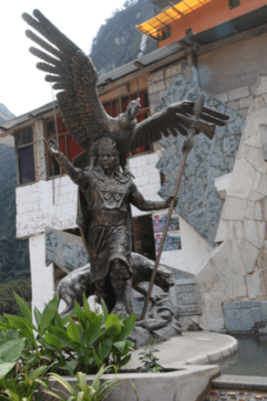 A statue of an Inca with a condor, puma, and snake