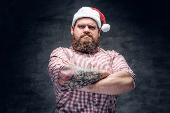 Brutal bearded male with tattooed arm wearing Santa's New Year hat.