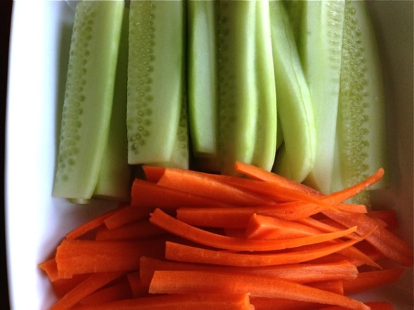 Peel the carrots and cucumbers. Cut in half and thinly slice.