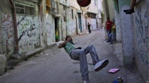 A Palestinian boy performs an overhead kick in an alley of Al-Amari refugee camp in the West Bank.