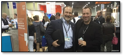 Trustmark's Jonathan Rogers and Eric Weikart in the Expo Hall. Notice the backlog at Q2's open bar in the background.