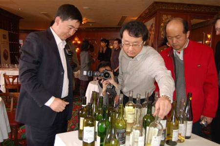 Judges Li Demei, Jin Yang, and Kong Wei Guo check the whites wines after they finish scoring.