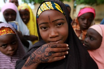 A girl displays traditional paintings on her hand in front of a local Koranic school on the second day of Ramadan in Nigeria's northern city of Kano, on July 21, 2012.