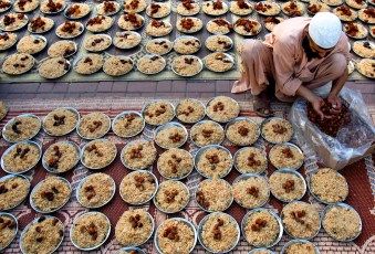 A man arranges plates with meals for Iftar, or breaking of the fast, donated by an Islamic seminary during the first day of Ramadan in Islamabad, Pakistan, on July 21, 2012.