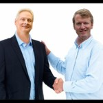Portrait of two businessmen shaking hands against white background