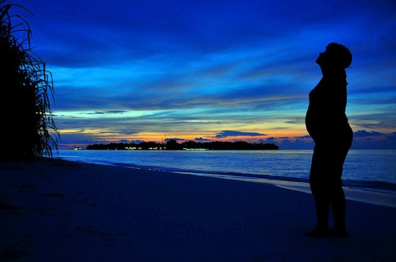 pregnant woman silhouetted against dramatic blue sky and beach