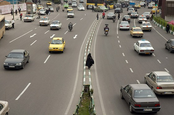 robed arab woman crossing road image