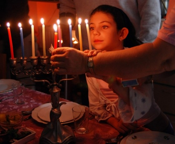 Girl watching lighting of Hannukah Mennorah
