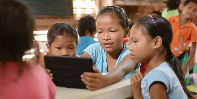 ALS Students reading from a tablet