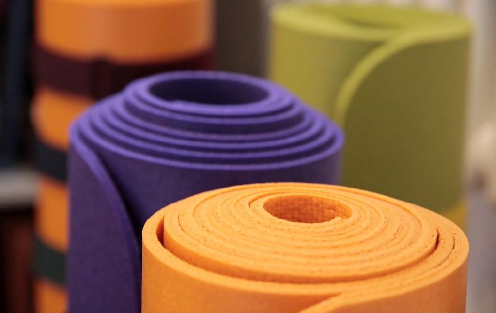 Bunte Yogamatten aufgerollt in einer Yoga-Schule