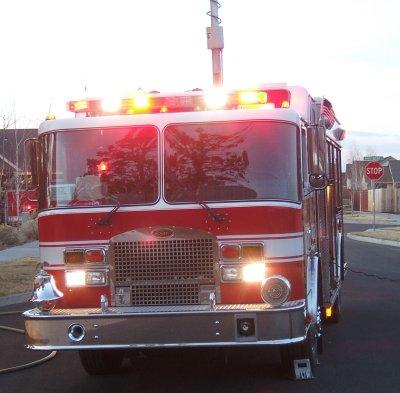Fire truck at dusk lighting up the scene