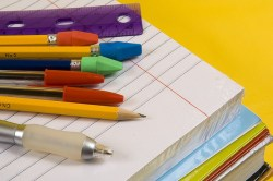 school supplies on yellow background with pen, pencils, rulers, paper and folders