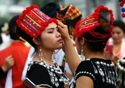 epaselect epa05905388 Kachin ethnic women help each other to get ready during the opening ceremony of the Thingyan Water Festival in Yangon, Myanmar, 13 April 2017. The annual water festival, known as Thingyan, features large groups of people congregating to celebrate the by splashing water and throwing powder at each other's faces as a symbol of cleansing and washing away the sins from the old year, and to mark the traditional New Year in countries such as Myanmar, Thailand, Laos and Cambodia. This year, the Myanmar Thingyan water festival runs from 13 to 16 April.  EPA/NYEIN CHAN NAING