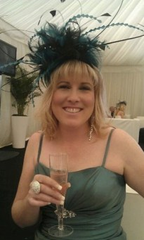 a picture of charley at a wedding in a big blue fascinator and with champagne in hand. She's smiling.