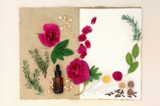 Love potion ingredients over natural hemp notebook and mottled cream paper background.