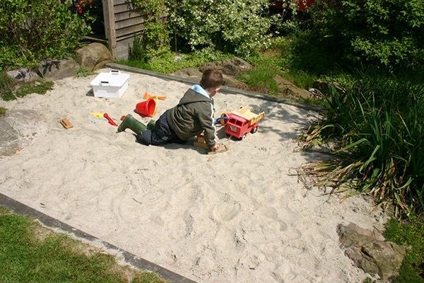 En sandkasse kan indgå i havens design.