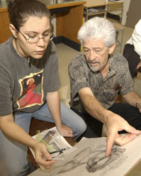 Female student discussing her drawing with white-haired professor