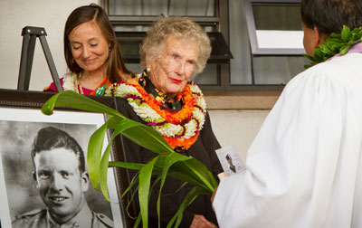 Elderly woman wearing lei with photo of young soldier outdoors facing minister with ti leaf