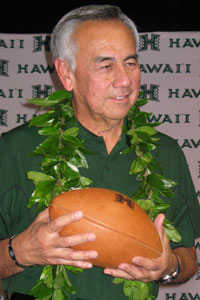 Norm Chow wearing maile lei and holding a football