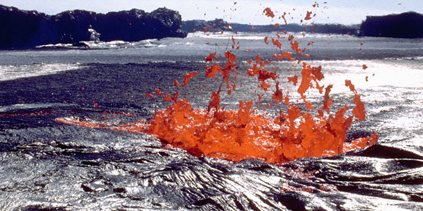red molten lava spurting from opening in black lava field