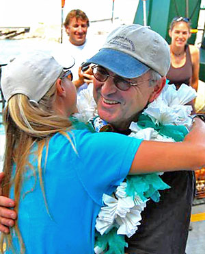 Smiling man with ball cap and large paper lei hugging a woman