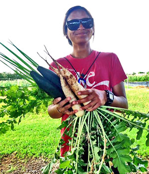 Agriculture student Chyane Kolish holds some of the vegetables grown by Hawaiʻi Community College students.