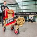 A butler is pictured with Heathrow's special royal golden luggage trolley. The baggage palace on wheels was created to celebrate the first birthday of Terminal 2: The Queen's Terminal and to mark the long association Heathrow has with Her Majesty The Queen.