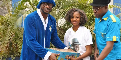 L-R, Olympic Milk Brand Ambassador, Peter Okoye of PSquare, dressed as Blue Santa presenting an autographed shirt and cartons of Olympic Milk to one of the winners of Blue Santa Selfie Challenge, Joy Orji, with Category Marketing Manager, Standard Milk, Nutricima Limited, Mr. Raphael Agbaje as part of activities to celebrate Xmas with consumers in Lagos on Sunday.