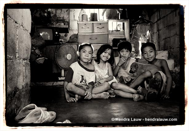 Children inside a 'house' at the Manila North Cemetery