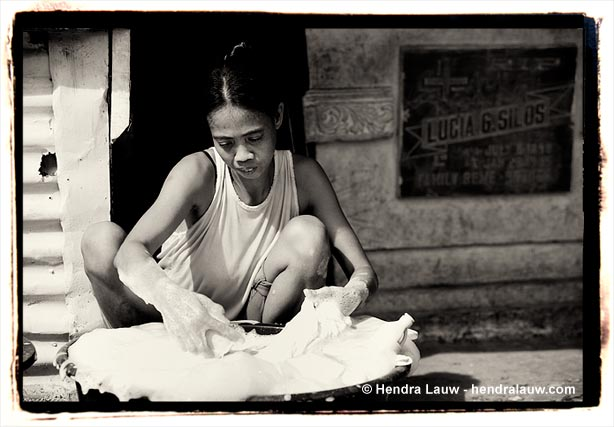 Washing clothes at the Manila North Cemetery